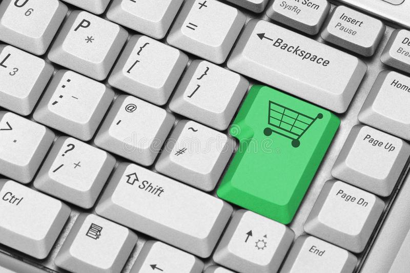Computer keyboard with shopping cart key in green stock photography