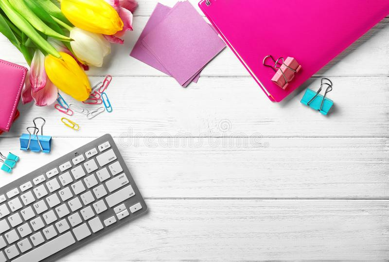 Computer keyboard, tulips and stationery on table, flat lay. Workplace composition stock photos