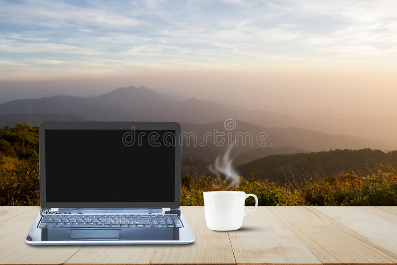 Computer laptop with black screen and hot coffee cup on wooden t stock photography