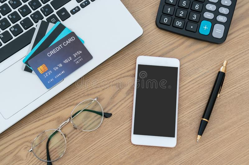 Computer laptop, credit cards, calculater, notbook pen and glasses on the desk, account and saving concept. Computer laptop, credit cards, calculator, notebook royalty free stock photo