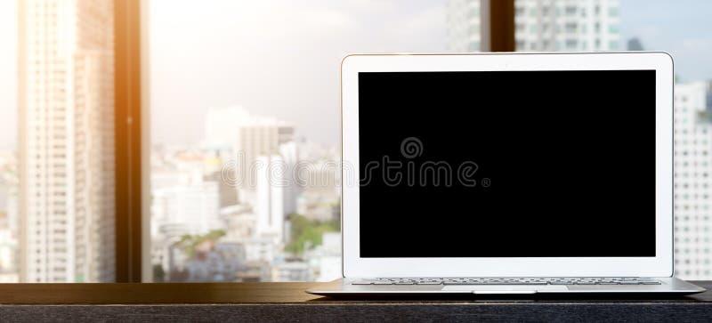 Computer, laptop met het lege scherm op houten lijst met de meningsachtergronden van het bureauvenster royalty-vrije stock foto