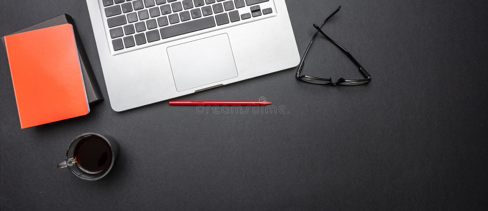 Computer laptop and mobile phone on black color office desk, banner royalty free stock photography