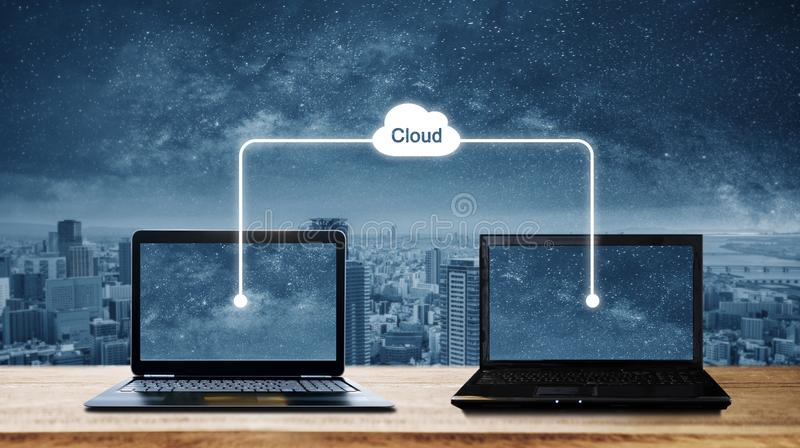 Computer laptops sharing data through cloud storage computing. Cloud computing and computer network concept royalty free stock image