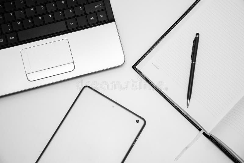 Computer met notitieboekje en pen en tablet stock fotografie