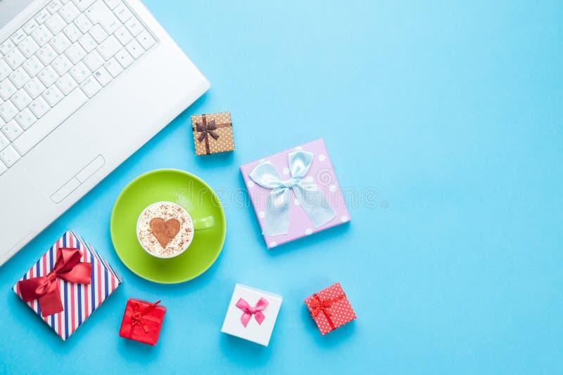 Computer mit Geschenkbxes und -cappuccino lizenzfreie stockbilder