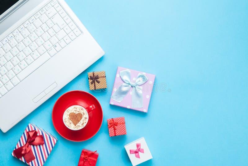 Computer mit Geschenkbxes und -cappuccino stockbild