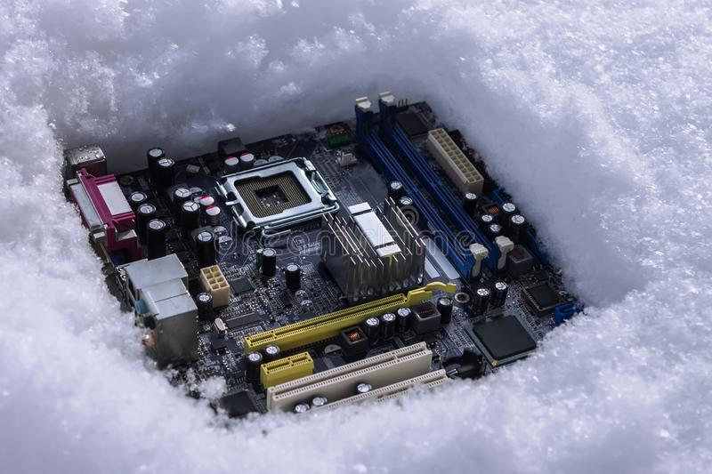 A computer motherboard with a processor lying on a dump in the snow, thrown out due to a malfunction royalty free stock image