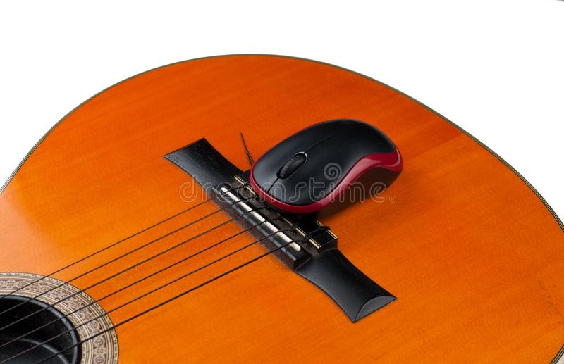 Computer mouse and guitar isolated on white background. Music, electronics, headphones, sound, screen, keypad, office, remote, laptop, plucking, instrument royalty free stock photography