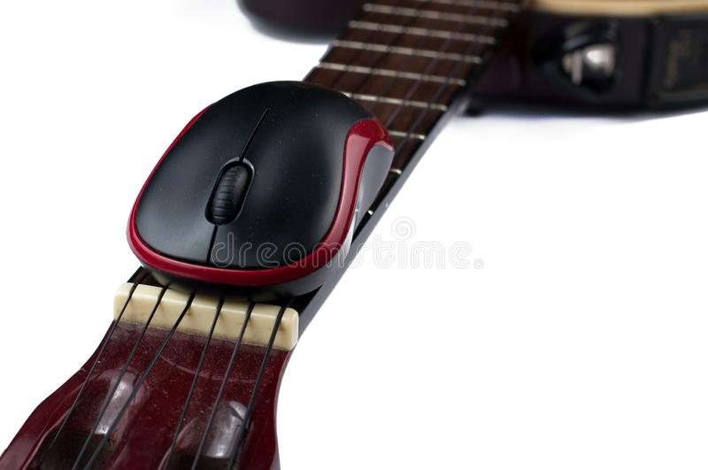 Computer mouse and guitar isolated on white background. Music, electronics, headphones, sound, screen, keypad, office, remote, laptop, plucking, instrument royalty free stock image