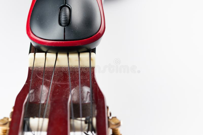 Computer mouse and guitar isolated on white background. Music, electronics, headphones, sound, screen, keypad, office, remote, laptop, plucking, instrument royalty free stock photos