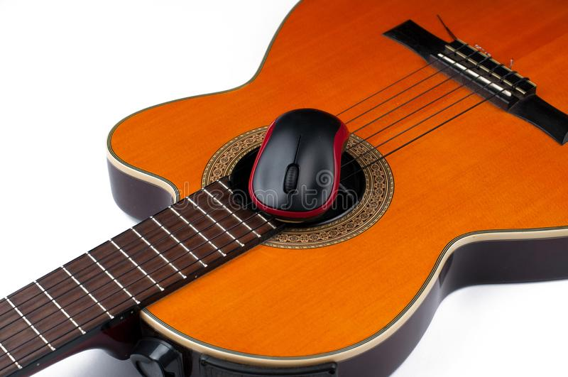 Computer mouse and guitar isolated on white background. Music, electronics, headphones, sound, screen, keypad, office, remote, laptop, plucking, instrument stock photo