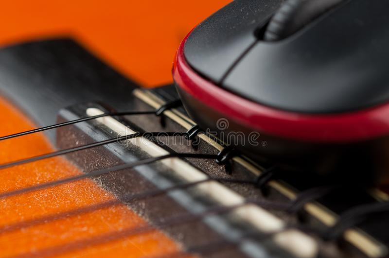 Computer mouse and guitar isolated on white background. Music, electronics, headphones, sound, screen, keypad, office, remote, laptop, plucking, instrument stock photography