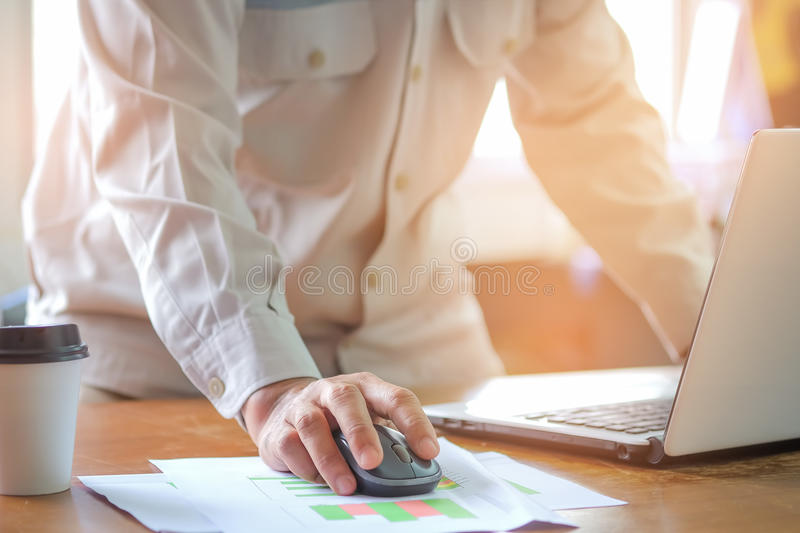 Computer mouse in hand, Man office staff are analyzing graphs. royalty free stock image