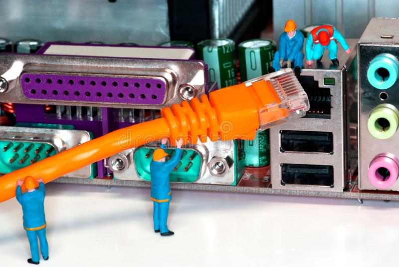 Computer Network Internet Cable. Miniature construction worker figurines posed as if working on a network connection royalty free stock photo