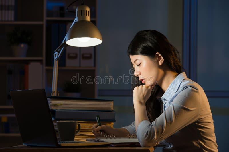Computer portatile asiatico di uso della donna di affari che funziona fuori orario a tarda notte immagini stock