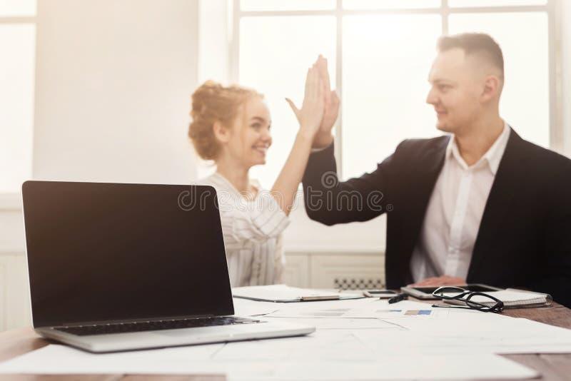 Computer portatile in bianco e fare felice della donna e dell'uomo alti--cinque fotografia stock libera da diritti