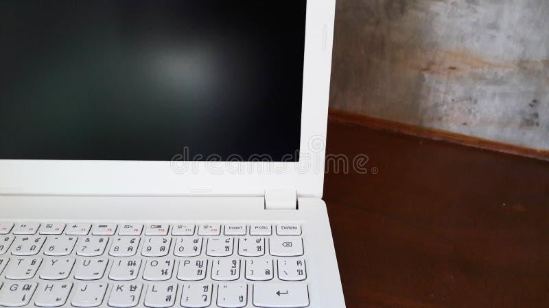 Computer portatile bianco sulla tavola di legno immagine stock