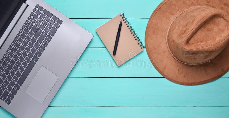 Computer portatile, cappello di feltro, taccuino e penna su una tavola di legno blu Concetto di giornalismo, vista superiore, dis fotografia stock