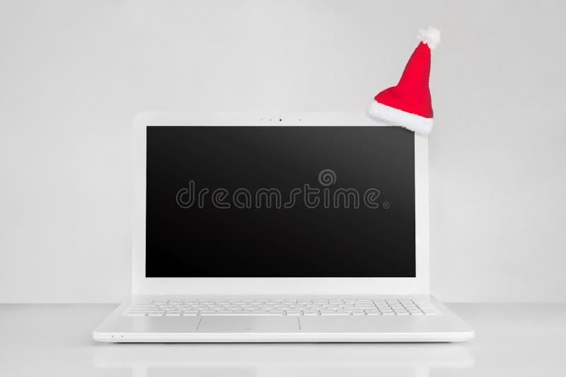 Computer portatile completamente bianco con il cappello rosso nero di Santa di natale e dello schermo concetto puro 2019 del nuov fotografia stock libera da diritti