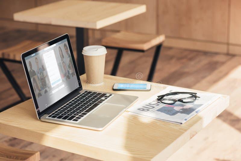 computer portatile con il sito Web del linkedin, smartphone con skype e giornale di affari sulla tavola immagini stock