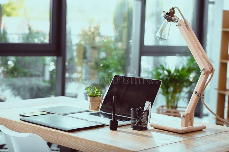 Computer portatile con la tavola e la lampada dei grafici con i fornitori dell'ufficio fotografie stock libere da diritti