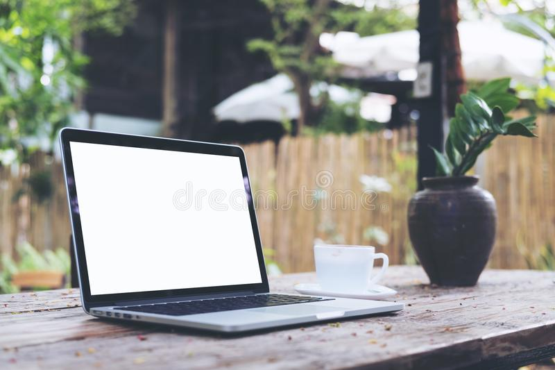Computer portatile con la tazza bianca in bianco di caffè e dello schermo sulla tavola di legno d'annata nel parco all'aperto del immagini stock libere da diritti