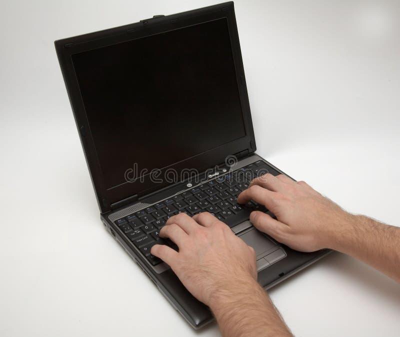 Computer portatile con le mani fotografia stock