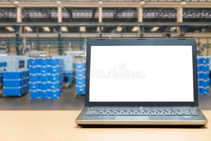Computer portatile con lo schermo in bianco sulla tavola con il carico del magazzino della sfuocatura fotografia stock