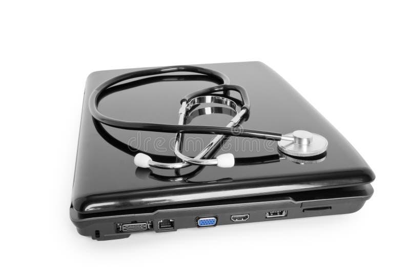 Computer portatile con lo stetoscopio fotografie stock libere da diritti