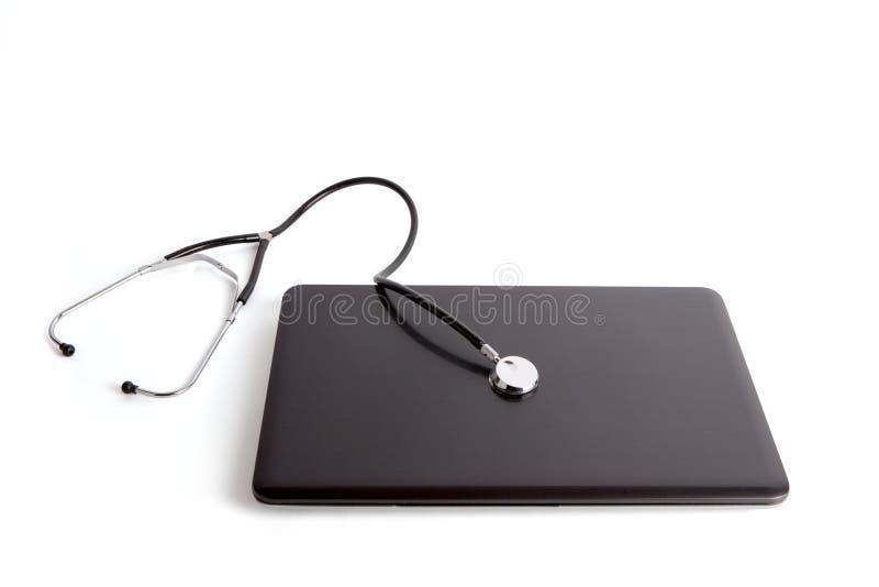 Computer portatile con lo stetoscopio isolato su fondo bianco immagini stock libere da diritti