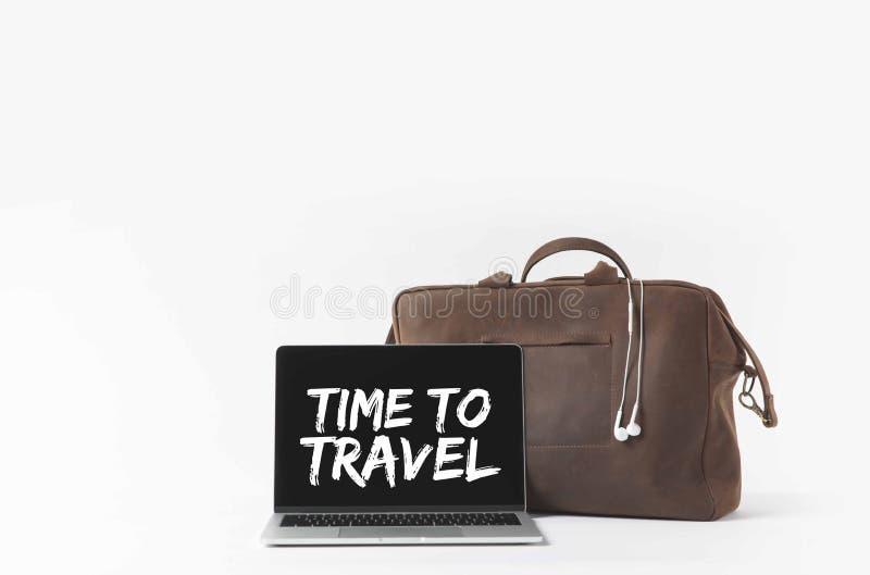 computer portatile con tempo di viaggiare ispirazione sullo schermo e borsa alla moda con le cuffie immagine stock