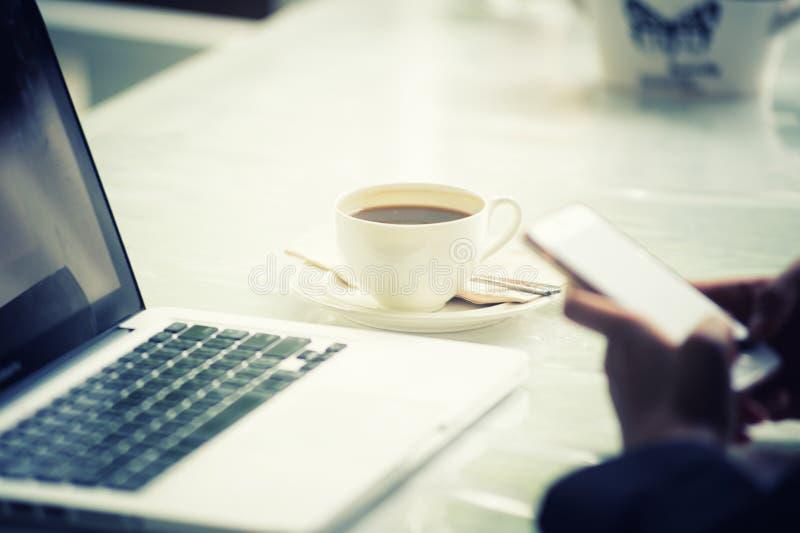Computer portatile del caffè e mano della donna di affari immagine stock