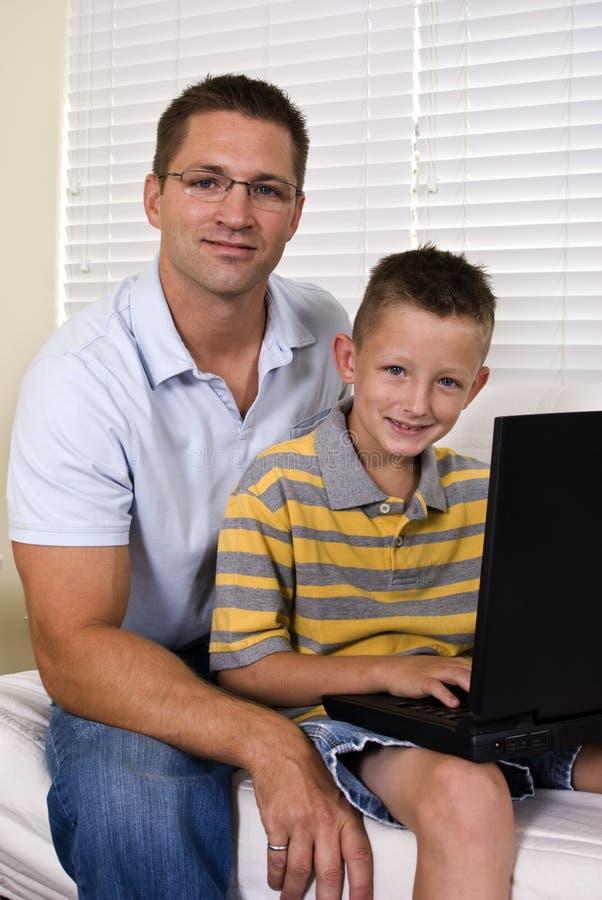 Computer portatile del papà e del figlio fotografie stock libere da diritti