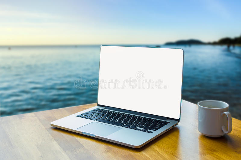 Computer portatile del primo piano sul fondo di legno della sfuocatura dello scrittorio immagini stock
