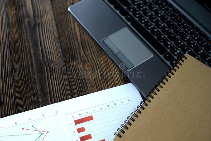 Computer portatile del taccuino e grafico finanziario su Libro Bianco su w fotografia stock