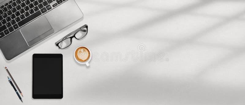 Computer portatile dell'area di lavoro dell'ufficio, compressa, vetri dell'occhio e caffè flatlay sul desktop bianco immagini stock libere da diritti