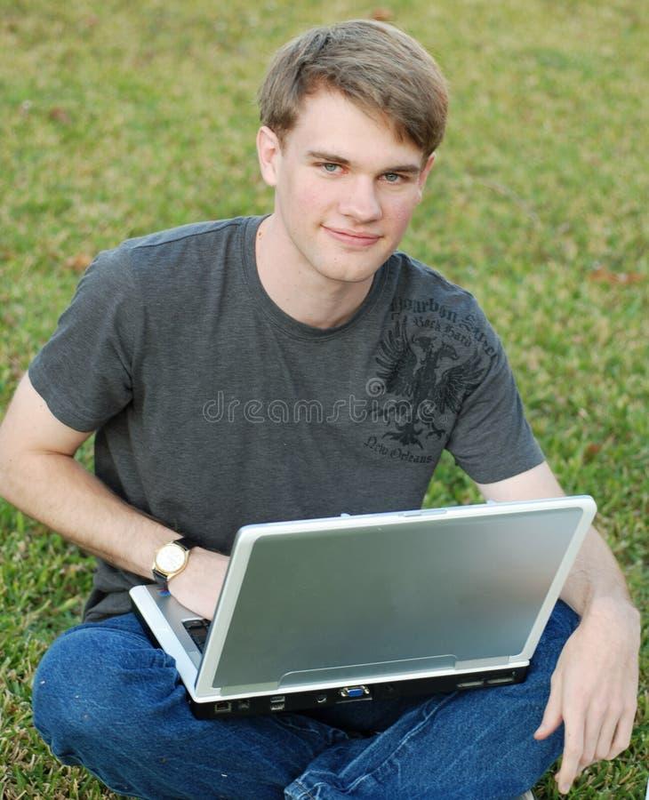 computer portatile dell'istituto universitario del ragazzo fotografia stock libera da diritti