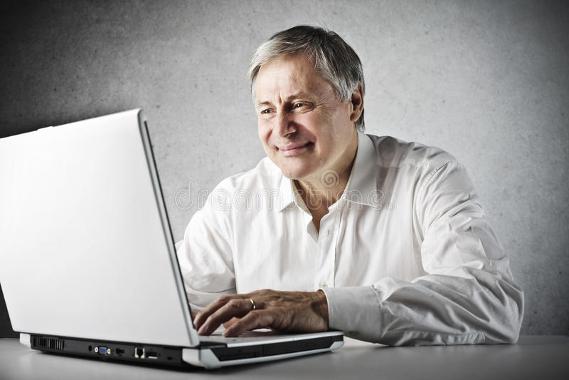 Computer portatile dell'uomo anziano fotografia stock