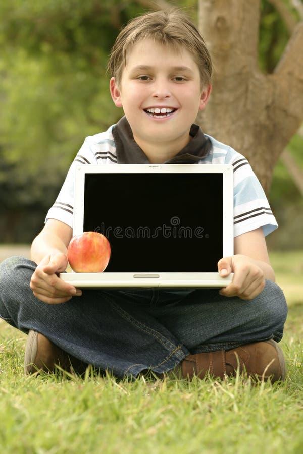 Computer portatile della holding del bambino con lo schermo in bianco fotografia stock