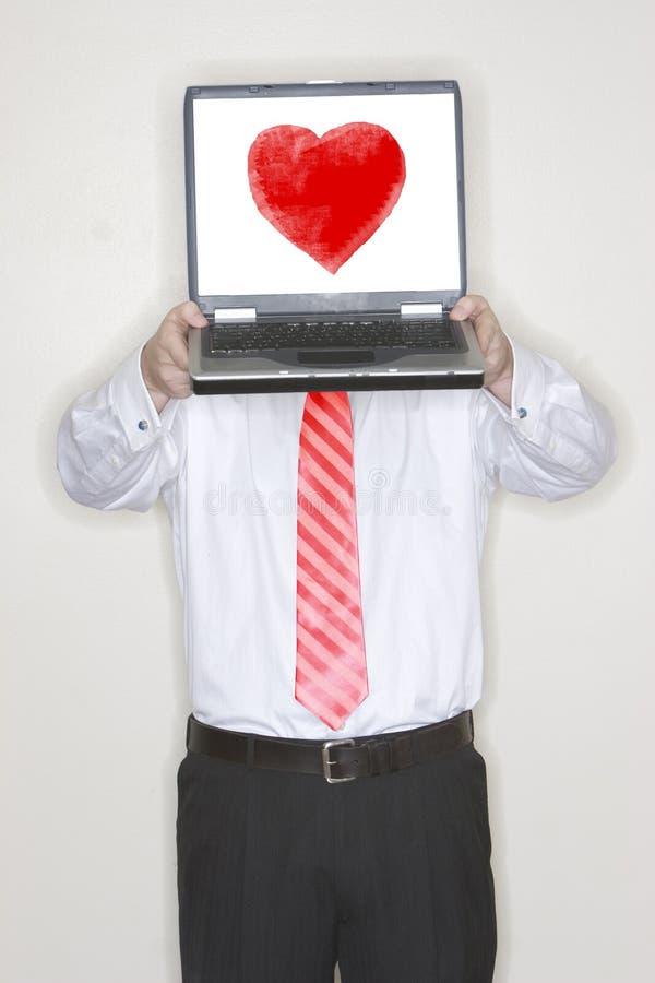 Computer portatile della holding dell'uomo d'affari con cuore fotografia stock libera da diritti