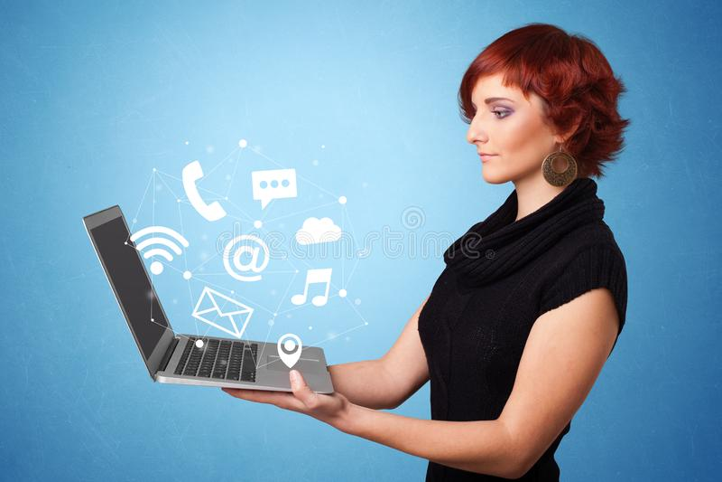Computer portatile della tenuta della donna con i simboli online immagine stock libera da diritti