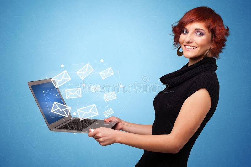 Computer portatile della tenuta della donna con i simboli online immagini stock libere da diritti