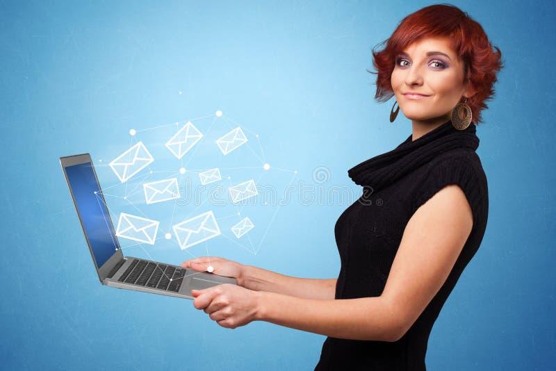 Computer portatile della tenuta della donna con i simboli online fotografia stock libera da diritti