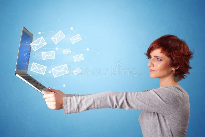 Computer portatile della tenuta della donna con i simboli online immagine stock