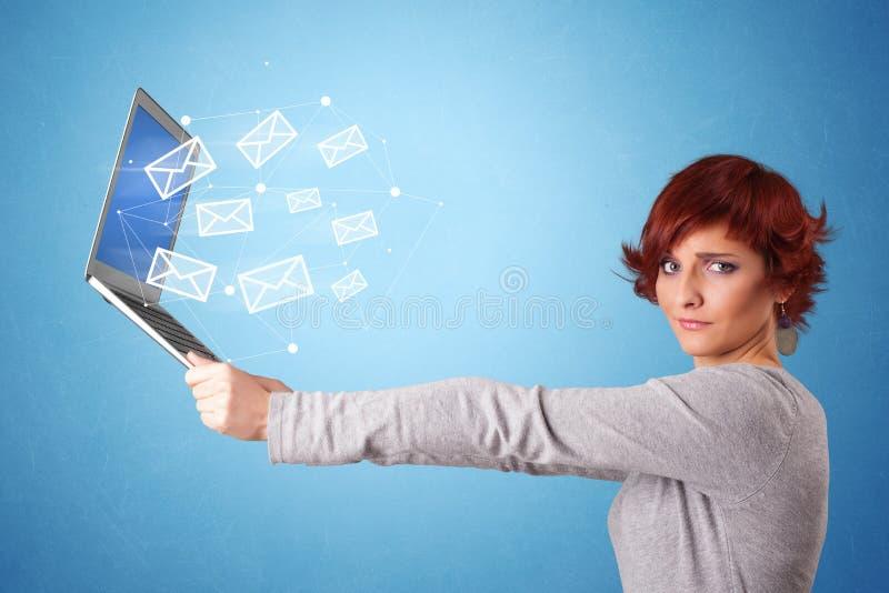 Computer portatile della tenuta della donna con i simboli online fotografia stock
