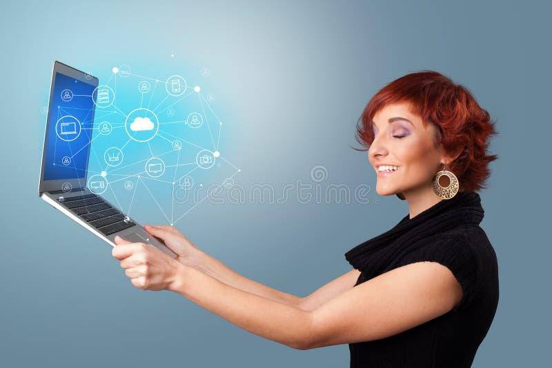 Computer portatile della tenuta della donna con il concetto di sistema basato nuvola fotografie stock