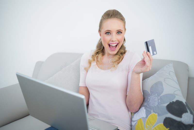 Computer portatile della tenuta e carta di credito biondi emozionanti casuali fotografie stock