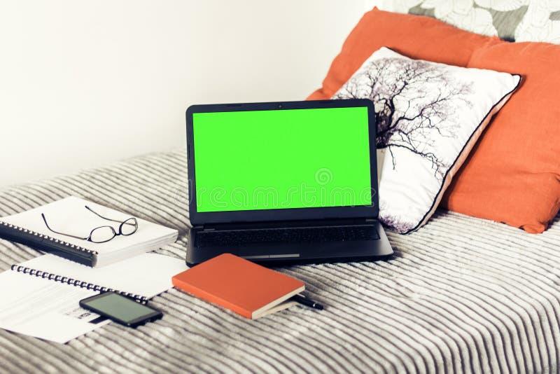 Computer portatile dello schermo, taccuino, smartphone, vetri e penna verdi su cattivo, fondo di concetto di istruzione fotografia stock libera da diritti