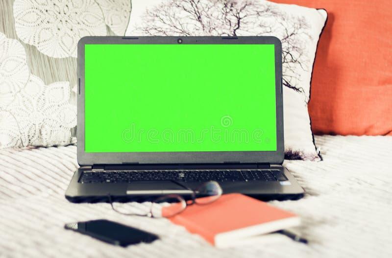 Computer portatile dello schermo, taccuino, smartphone, vetri e penna verdi su cattivo, fondo di concetto di istruzione immagini stock libere da diritti