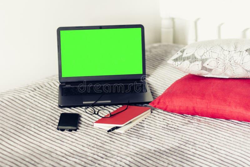Computer portatile dello schermo, taccuino, smartphone, vetri e penna verdi su cattivo, fondo di concetto di istruzione immagini stock